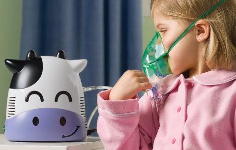 Девочка дышит через детский небулайзер